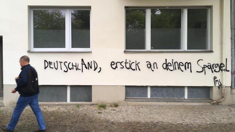 Un homme passe devant un graffiti sur le mur d'un immeuble, qui dit: « Allemagne, étouffe-toi avec tes asperges »