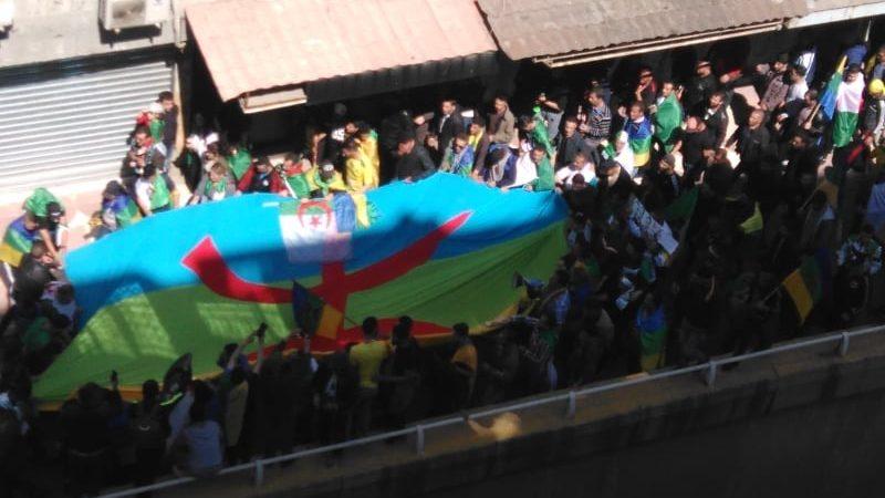 Vue plongeante sur une foule de manifestants portant un immanse drapeau amazigh sur lequel est posé un minuscule drapeau algérien.