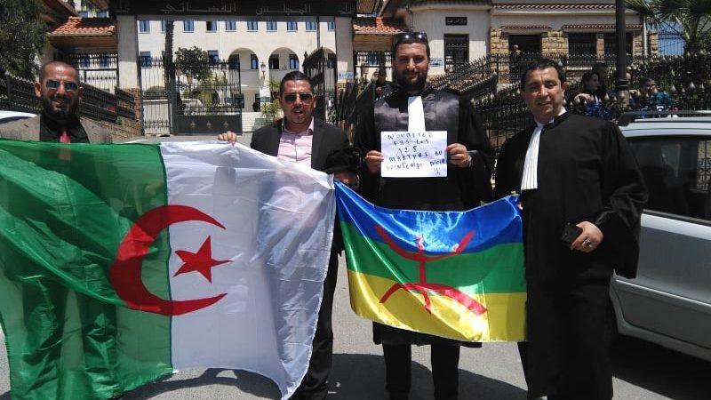 Quatre manifestants amazigh, dont deux portent une toge d'avocat et les deux autres sont en costume-cravate.