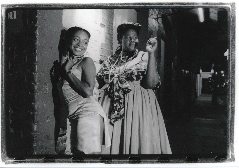 Deux femmes parées pour sortir s'appuient contre un mur, le regard hors champ. L'une sourit de façon avenante tandis que l'autre fume une cigarette, l'air impassible.
