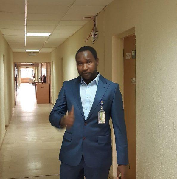 Mubarak Bala, vêtu d'un costume bleu, dans un couloir de bureaux. Un badge est accroché à sa veste.