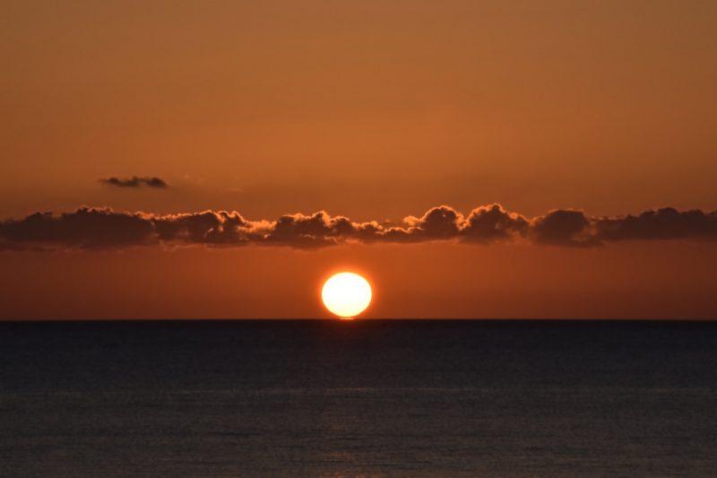 Le soleil se couche sur l'océan, sous un bandeau de nuages.