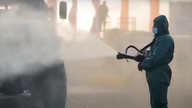 Un militaire égyptien vêtu d'une combinaison de protection intégrale et d'un masque facial pulvérise un camion pour le désinfecter.