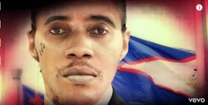 Visage de Vybz Kartel, impassible, devant un drapeau.