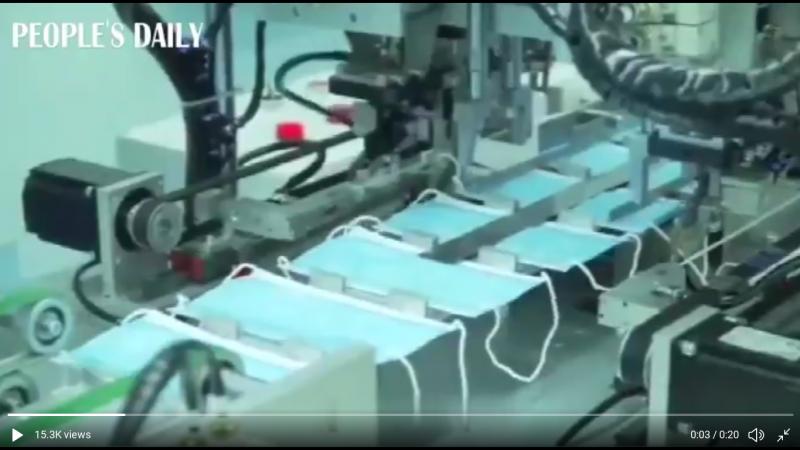 Une chaîne de fabrication de masques de protection faciaux. Un ouvrier masqué vérifie le produit.