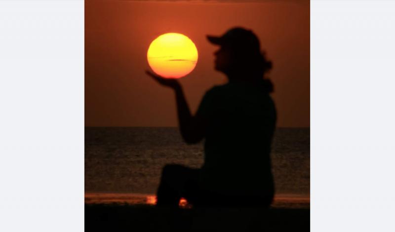 Au coucher de soleil, une femme semble tenir le soleil dans sa main.
