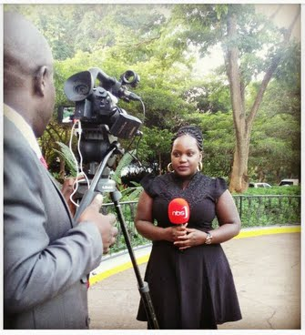 Bahati Remmy lors du tournage d'une émission de NBS. Debout dans une allée verdoyante, elle tient le micro dans ses mains tandis que le cameraman la filme.