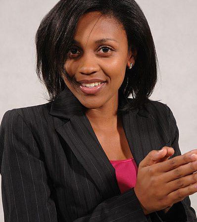 Portrait de la journaliste ougandaise Joy Doreen Biira, souriante, les mains jointes devant la poitrine.