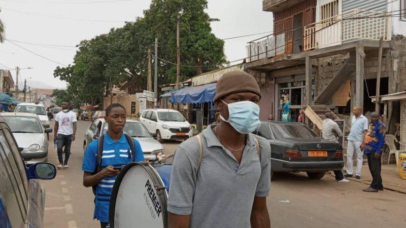 Plusieurs hommes marchent au milieu de la circulation dans une rue de Yaoundé. L'un d'eux transporte une batterie et porte un masque de protection faciale.