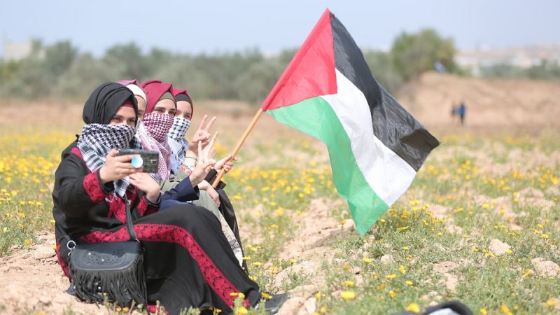 Quatre femmes, le bas du visage couvert, se prennent en photo dans un champ avec le drapeau palestinien.