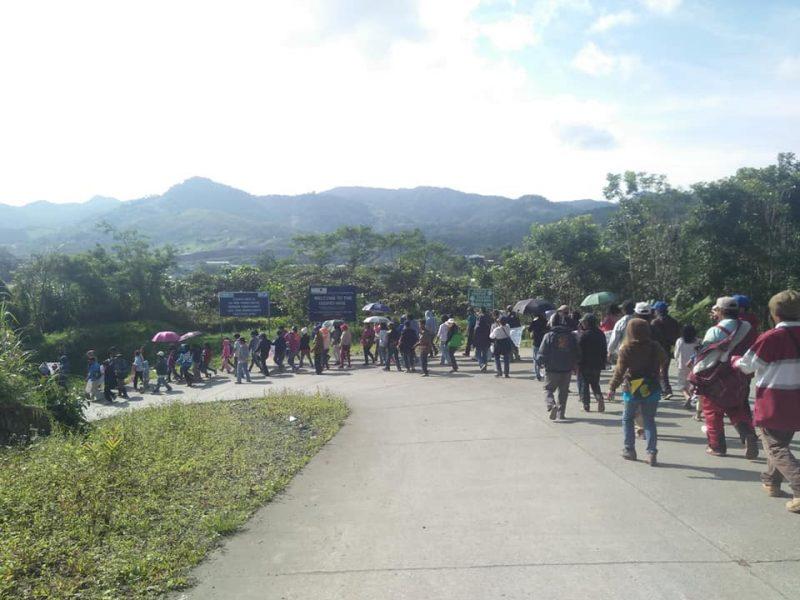 Sur une route de montagne, une file de manifestants prend un virage.