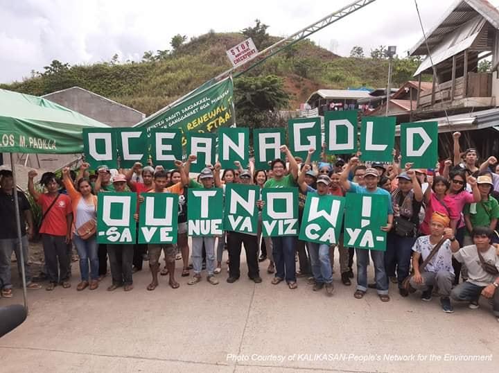 """Des manifestants tiennent une pancarte indiquant: """"Ocean Gold Dégage, Sauvez Nueva Vizcaya"""""""