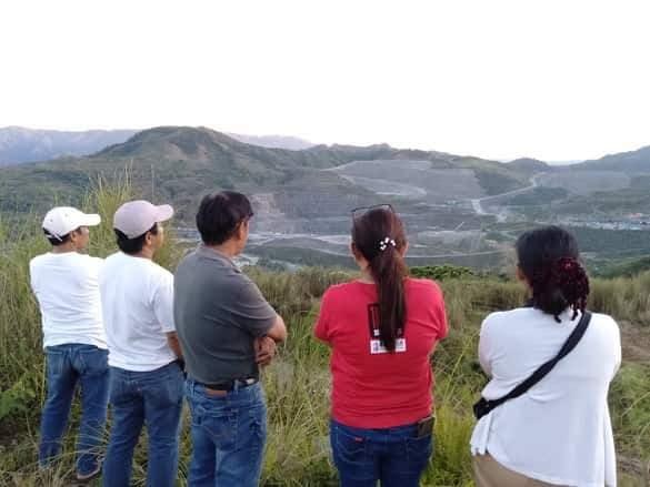 Cinq résidents de Nueva Vizcaya, de dos, fixent l'horizon.
