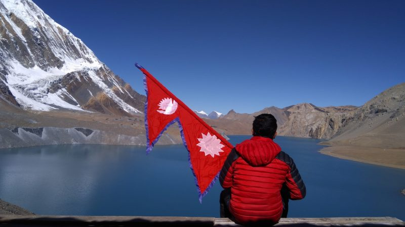 A man is sitting at the banks of Tilicho lake, Nepal, holding a Nepali flag. Image via Pxfuel, used under a Creative Commons Zero - CC0 license.