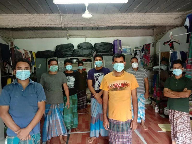Dans une chambre de dortoir étroite, se tiennent huit hommes, avec des masques de protection faciale.