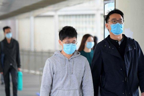 Des hongkongais portant des masques chirurgicaux dans l'espace public