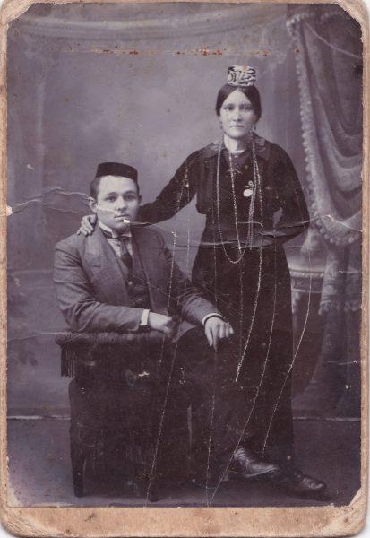 Une femme debout, portant un petit couvre-chef, tient par l'épaule un homme assis, vêtu d'un costume-cravate. La pose est solennelle.