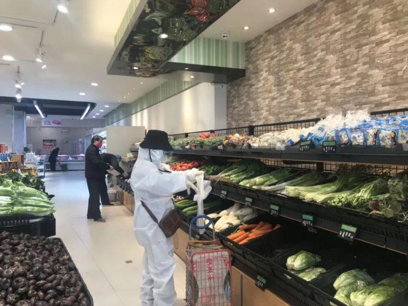 Quelques rares clients sont à l'intérieur d'un supermarché. Une personne, portant un équipement de protection complet avec un chapeau noir sur la tête, se trouve au rayon des fruits et légumes.