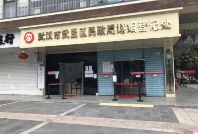 On distingue la devanture d'un commerce/bureau administratif. On peut voir une inscription en chinois sur le haut du commerce. Quelques affiches sont visibles sur les vitres. La rue est déserte.