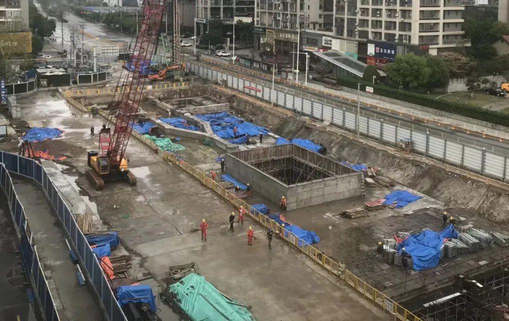 Un chantier de construction, sous un ciel pluvieux, barricadé par des panneaux bleus et blancs.. On distingue une grue et des hommes ainsi que les fondations d'un bâtiment.