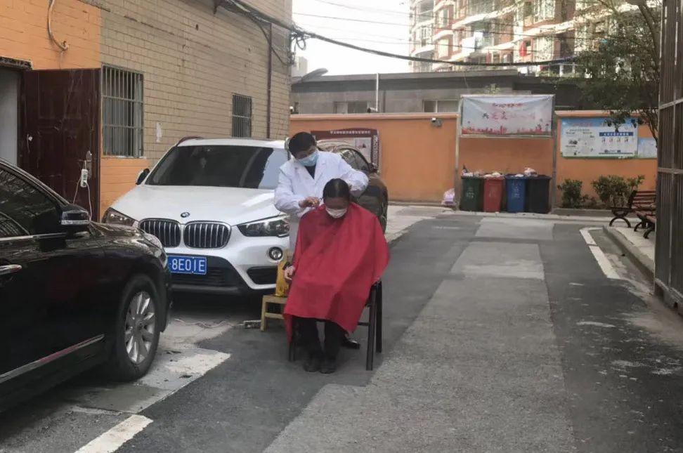 Un coiffeur coupe les cheveux d'un homme dans une rue déserte.