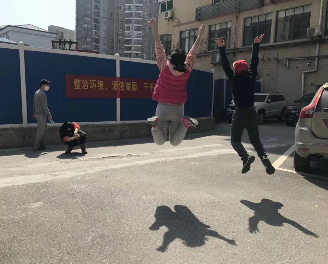 Deux personnes sautent en l'air dans un parking en bas d'un immeuble tandis que leur ami, accroupi, les prend en photo.