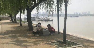 Trois femmes sont accroupies et piquent-niquent au bord d'une rivière, à l'ombre, sous les arbres. On distingue des bateaux, au loin.