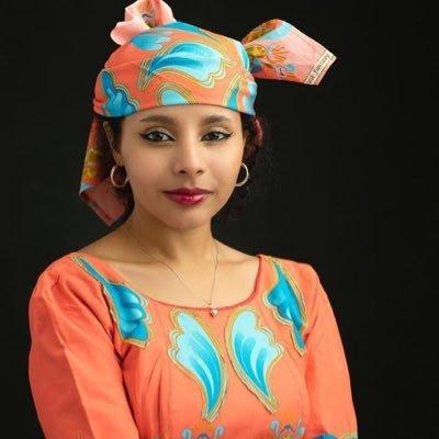Portrait de l'activiste nigériane Fakhriyyah Hashim, en robe et foulard de tête assortis. Elle porte des bijoux et du maquillage.