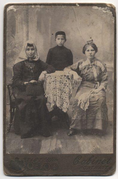 Deux femmes en robe longue sont assises à une table, un jeune garçon portant un keffieh debout entre elles.