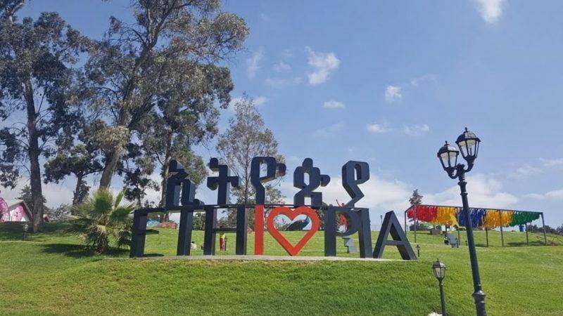 """Sur une pelouse du Parc de l'unité à Addis Abeba, un panneau porte le mot """"Ethiopie"""" en anglais et en amharique. Le o d'Ethiopie est en forme de coeur, les deux lettres i et o forment """"I <3"""""""