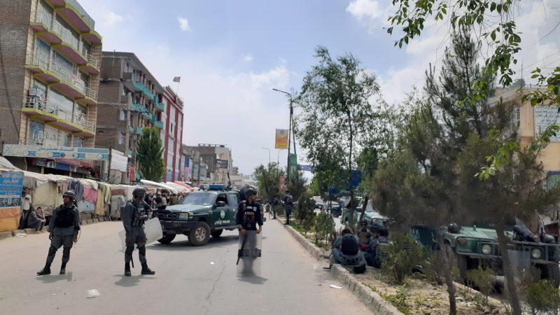 """""""une rue de Kaboul en Afghanistan avec des hommes et un véhicule des forces de sécurité qui barre la route"""""""