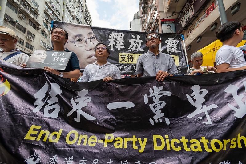 Vue serrée, en contre-plongée de manifestants défilant à Hong-Kong. Ils portent une banderole exprimant leur mécontentement. On distingue des buildings tout autour d'eux.