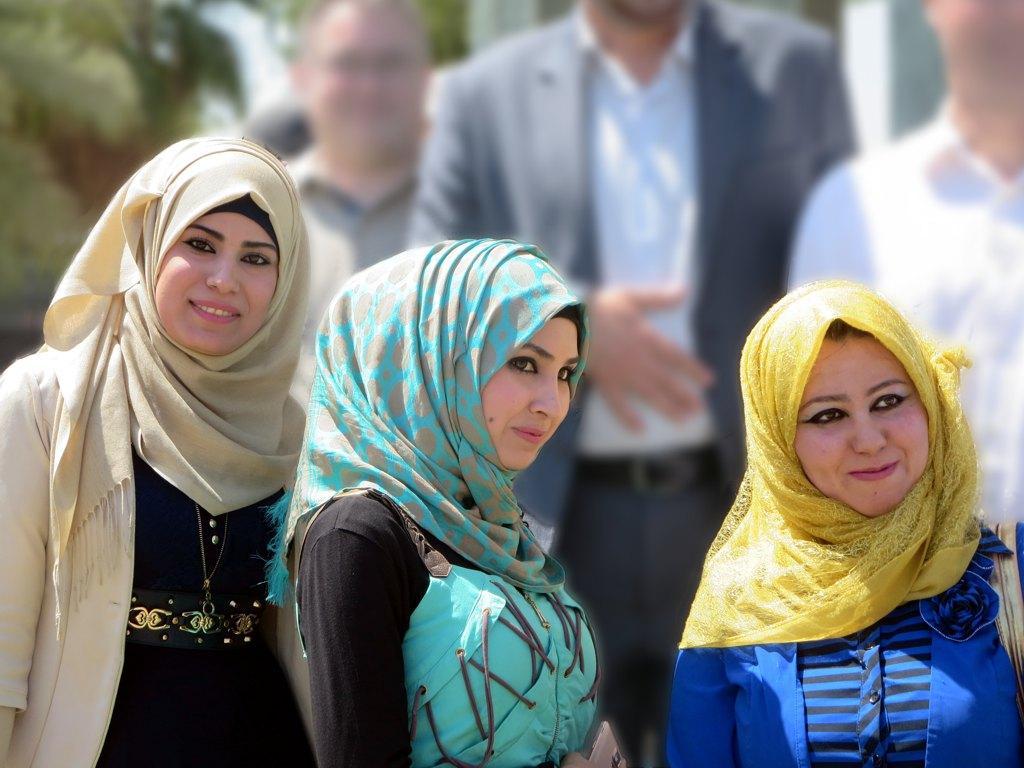 Trois jeunes femmes iraquiennes, portant des robes et des hijabs colorés, posent pour la caméra.