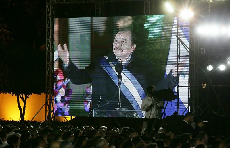 On distingue un écran géant sur lequel est retransmis le discours inaugural du président Daniel Ortega. En premier plan, une foule de personnes se trouve devant et à coté de cet écran. Des projecteurs sont visibles et la nuit est tombée. Sur la droite de l'écran, se tient un cameraman filmant et retransmettant l'événement. Sur la gauche de l'écran, on aperçoit des arbres.