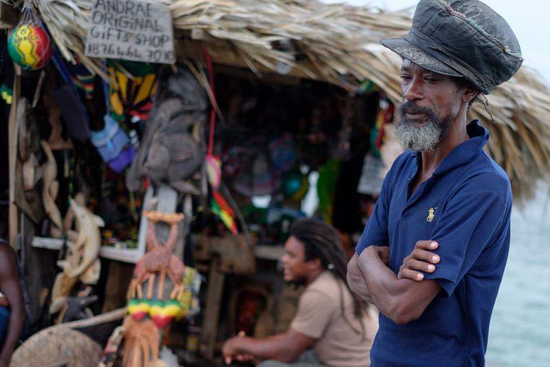 Un jamaïcain, les bras croisés, les yeux tournés vers le sol, devant une échoppe.