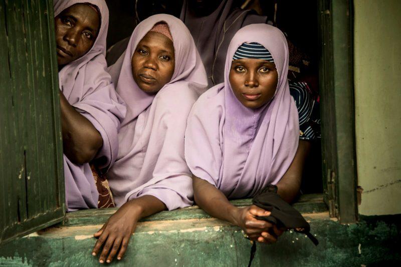 Trois femmes nigérianes en hijab mauve sont penchées à une fenêtre.