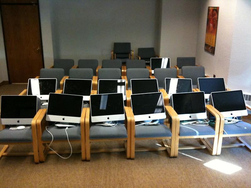 Sur des sièges alignés sur plusieurs rangs se trouvent des écrant d'ordinateur.