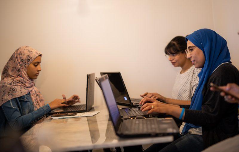 Trois femmes sont assises autour d'une table, devant des ordinateurs portables.