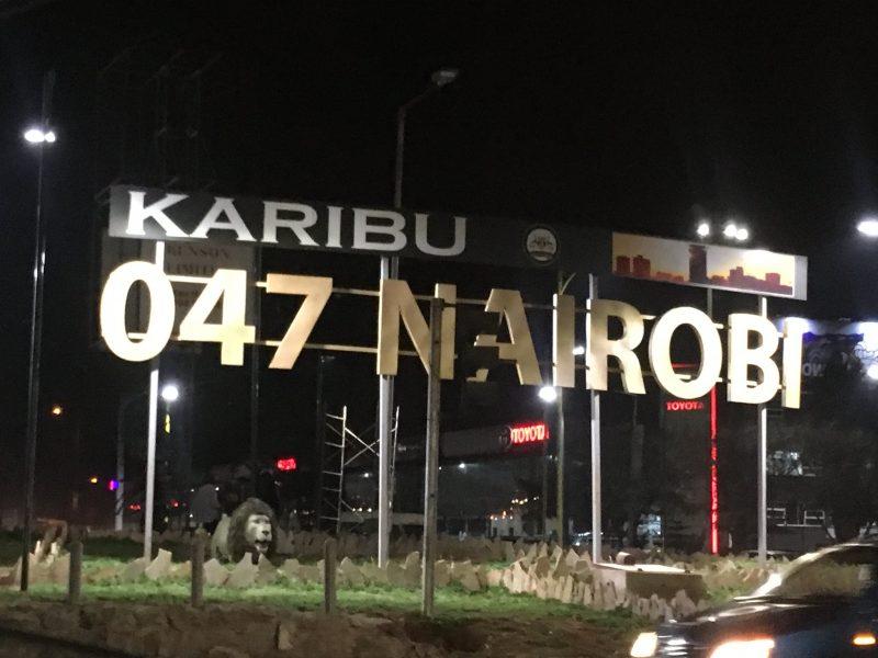 """Au-dessus d'un rond-point où se trouve une petite statue de lion trône un énorme panneau éclairé proclamant : """"Bienvenue à Nairobi"""" en swahili."""