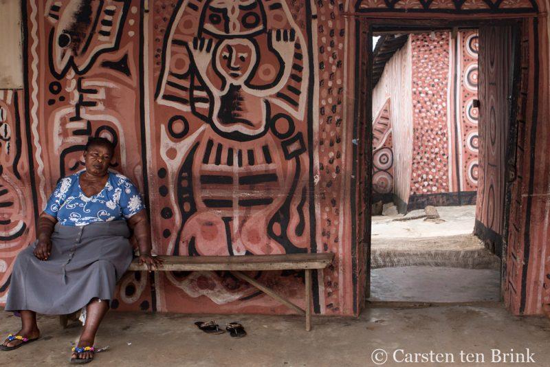 Une prêtresse nigériane, vêtue d'une chemise et une jupe ordinaires, est assise sur un banc en bois à l'entrée d'un temple dont les murs sont peints de motifs aux couleurs rougeâtre, noir et blanc.
