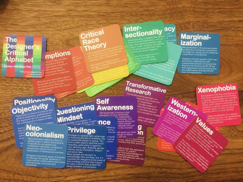 Des cartes colorées sont étalées sur une table, chacune comportant le nom d'un concept pertinent à la démarche design ainsi que sa définition.