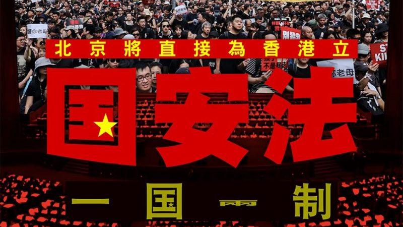 Gros plan de caractères chinois en rouge et en jaune sur une banderole de rue. En arrière plan, une foule compacte de manifestants.