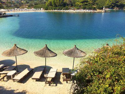 La plage privée de l'hôtel Abalone avec ses transats et parasols en paille tressée. L'eau est limpide.