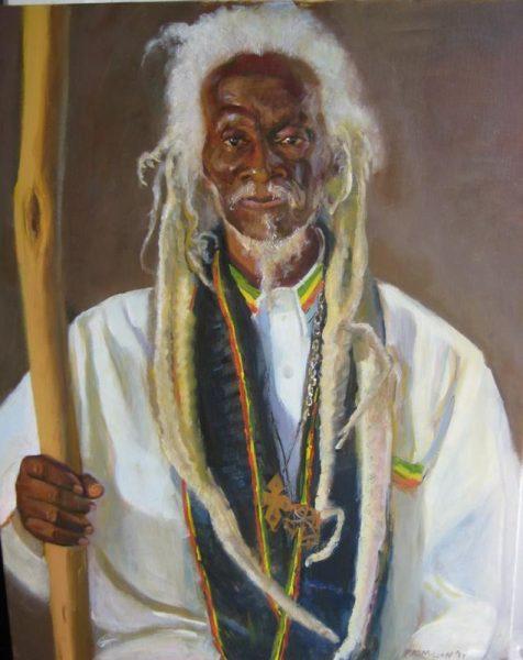 Un vieil homme aux longues dreadlocks blanches porte un grand bâton ainsi que des symboles du mouvement Rastafari.