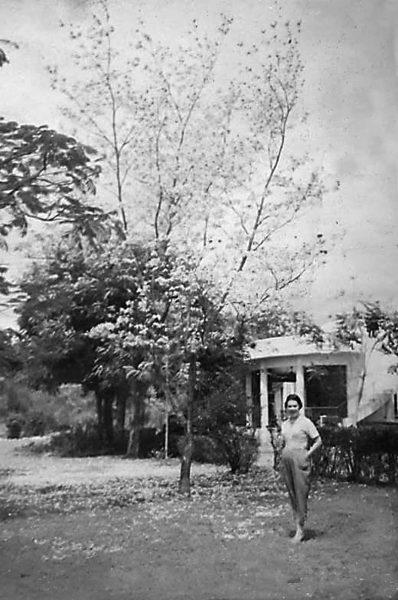 La mère de l'artiste pose debout dans un jardin arboré, devant une maison blanche. Elle porte un t-shirt et un pantalon ample.