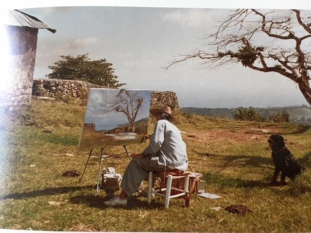 Assise devant son chevalet, l'artiste peint la campagne environnante. On distingue une maison et un mur en pierre.