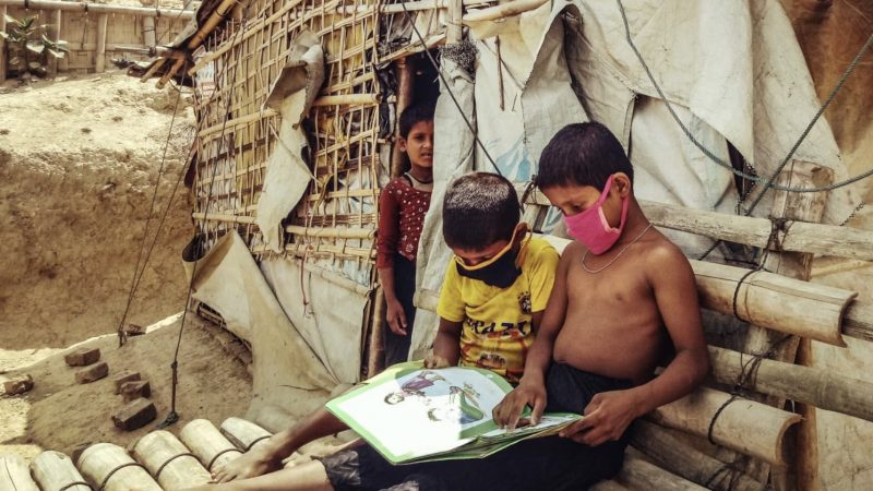 During Covid-19 lockdown, Rohingya children reading in front of their camp home, Cox's Bazar, Bangladesh. Submission by Abul Kalam. Used with permission. Dum la KOVIM-19 kvaranteno, rohinĝaj infanoj estas legantaj fronte al ilia rifuĝeja hejmo, Koks Bazar, Bangladeŝo. Sendita de Abul Kalam. Uzata kun permeso.