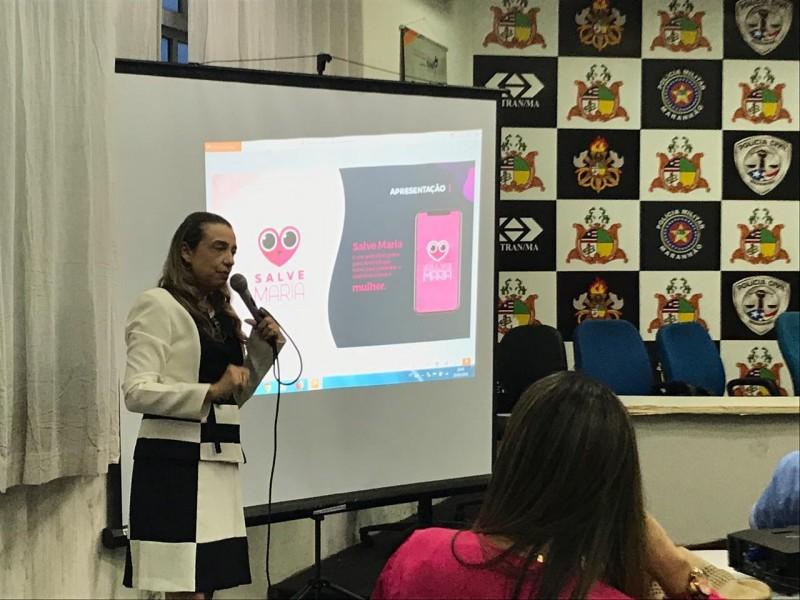 Vêtue d'un costume noir et blanc, Eugênia Villa donne une présentation. Derrière elle sont affichés des logos, dont celui de la police civile.