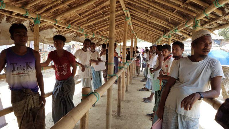 Sous un abri en bambou, des réfugiés rohingya font la queue à un mètre de distance les uns des autres pendant la pandémie de COVID-19.