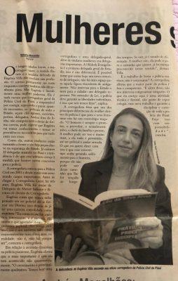 Une coupure de journal montre Eugênia, les cheveux détachés, tenant un livre ouvert.